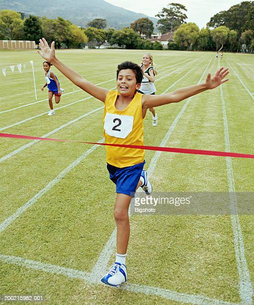 Boy (10-12) crossing finishing line on running track, smiling