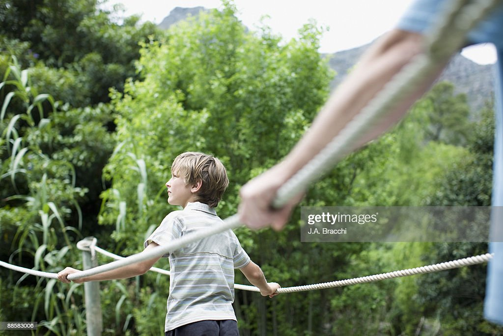 Boy crossing footbridge in remote area : Stock Photo