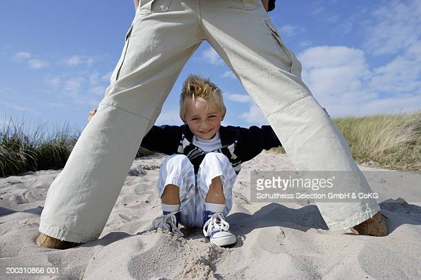 Boy (4-6) crouching on beach, view between father's legs, portrait