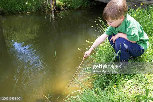 Boy (3-5) crouching on riverbank, poking stick in water