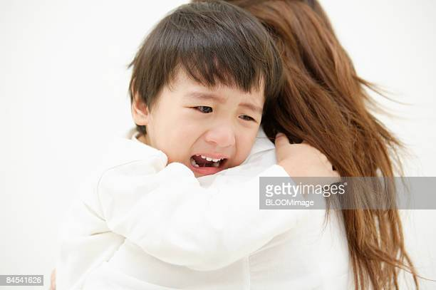 Boy crying, clinging to mother