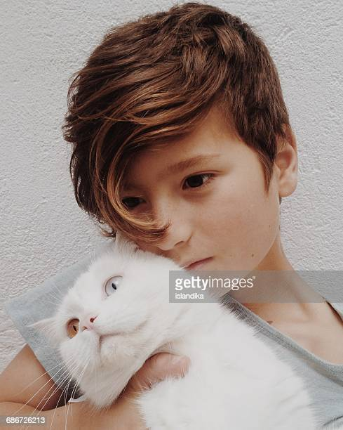 Boy cuddling his pet cat with different colored eyes