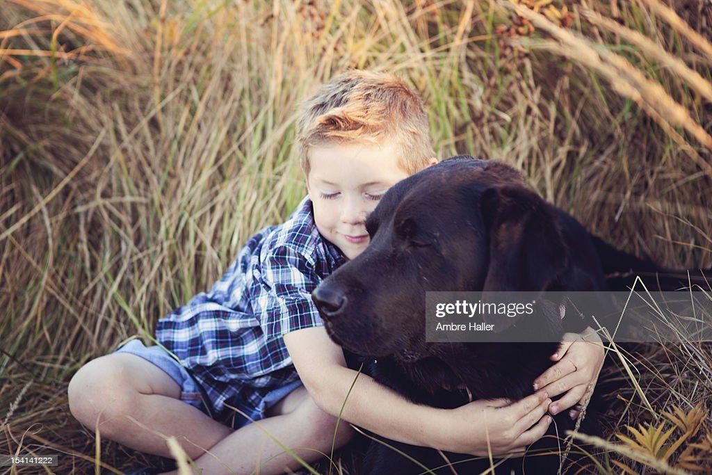 Boy cuddling with his dog : Stock Photo