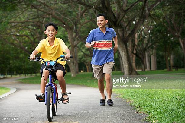 Boy cycling, father running behind him