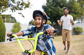 Boy cycling with father gesturing while standing in background