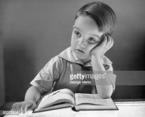 Boy daydreaming at desk : Stock Photo