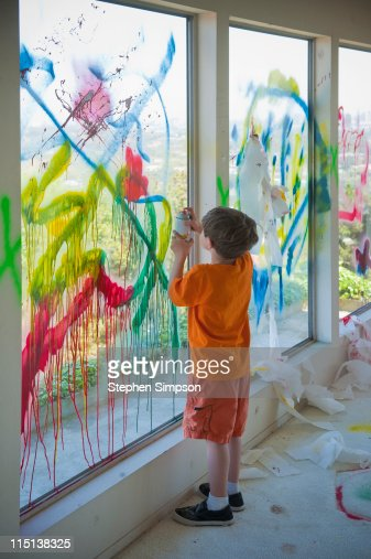 boy decorating windows with paint and paper : Stock Photo