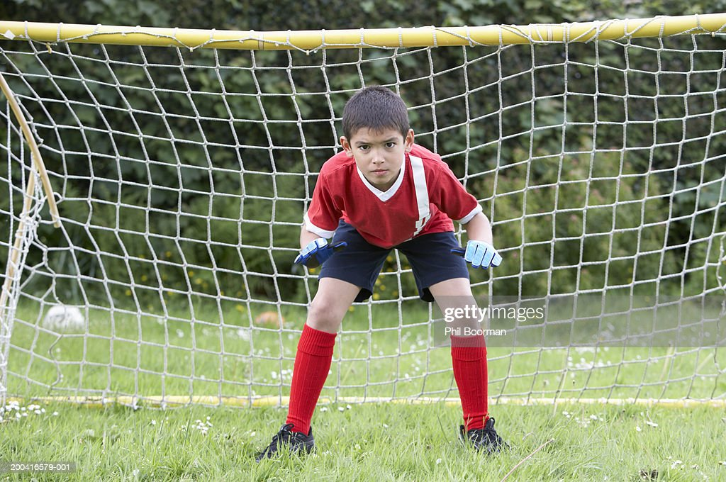 Boy (8-10) defending football goal : Stock Photo