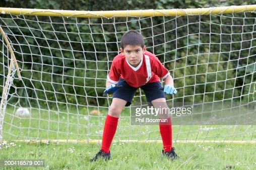 Boy (8-10) defending football goal : Stock Photo