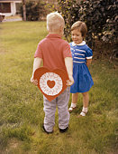 Boy delivering Valentine heart to smiling girl