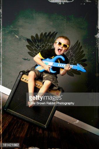 Boy demon sat on an amp with toy guitar : Bildbanksbilder