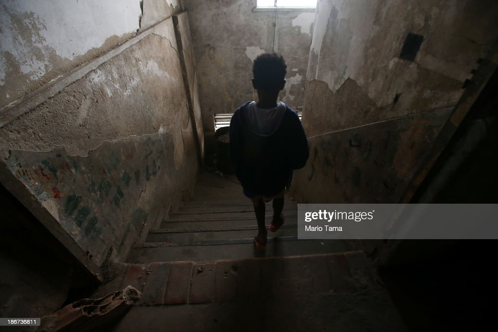 A boy descends a stairwell in a formerly deserted bullding which is currently home to 82 families who occupy the building in the port district on November 3, 2013 in Rio de Janeiro, Brazil. Residents say the building has been occupied for the past 14 years and government officials have informed the residents that they will be relocated to new housing in the North Zone of the city ahead of the 2014 World Cup. Some residents doubt the intentions of the government. Ahead of the 2014 World Cup and Rio 2016 Olympic Games, Rio has started a multibillion dollar urban renewal program of its port district which includes a double decker waterfront freeway being torn down to be replaced by tunnels, repaved roads, a tram network and other infrastructure improvements in the area. The 'Porto Maravilha' project is also expected to displace around 1,000 local residents.