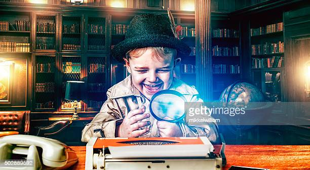 Boy detective with magnifying glass at work