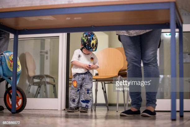 Boy Dilllen waits next to his mother as she casts her ballot in state elections in North RhineWestphalia on May 14 2017 in Muehlheim an der Ruhr...