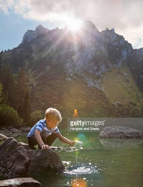 Boy dipping mug into still lake