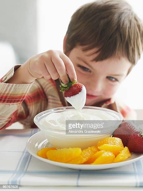 Boy Dipping Strawberry in Yogurt