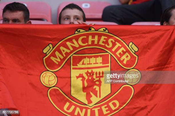 A boy displays a Manchester United flag prior to the UEFA Super Cup football match between Real Madrid and Manchester United on August 8 at the...