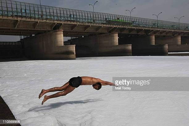 A boy dives into a dirty foamy Yamuna river near the Okhla barrage A study has found out that the level of contamination in the capital's water has...