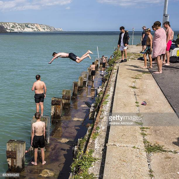 A boy dives off Folkestone Harbour into the sea water with his friends watching after the annual Trawler race and fun day in Folkestone Kent England...