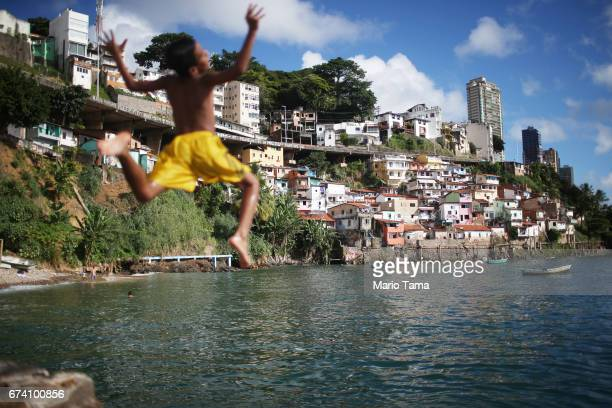 A boy dives off the rocks in front of the Gamboa de Baixo community on April 18 2015 in Salvador Brazil