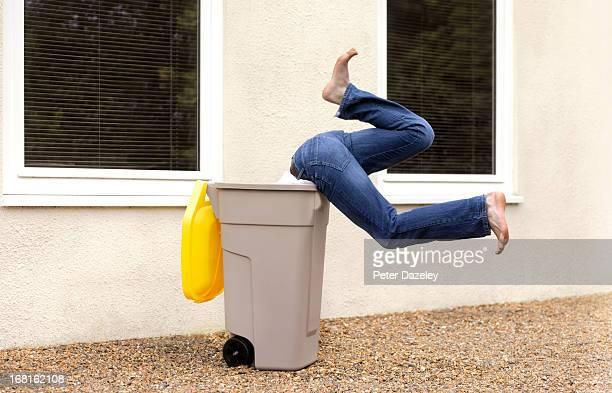 Boy diving into recycling bin