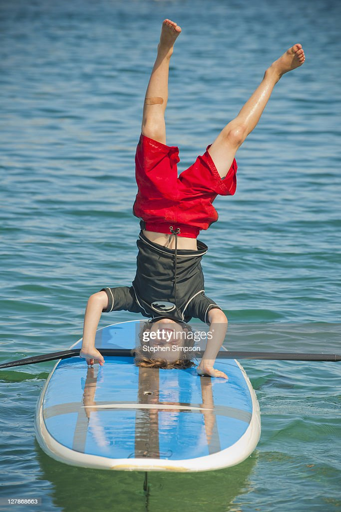 boy doing a headstand on paddle board : Stock Photo