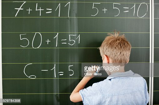 Boy doing arithmetic on blackboard : Stock Photo