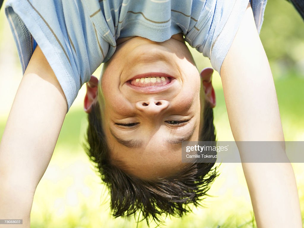 Boy (6-7) doing handstand in park, close up, close-up : Stock Photo