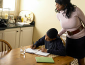 Boy (12-13) doing homework at kitchen table, mother looking over shoulder