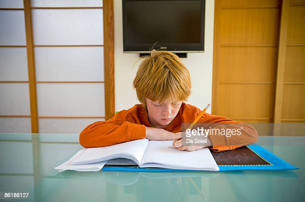 boy doing homework at kitchen table