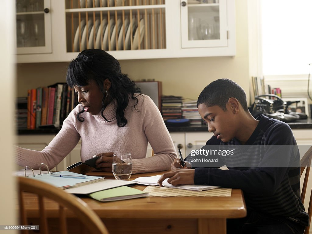 Boy (12-13) doing homework by mother using calculator at kitchen