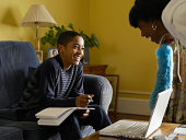 Boy (12-13) doing homework in living room, smiling to mother