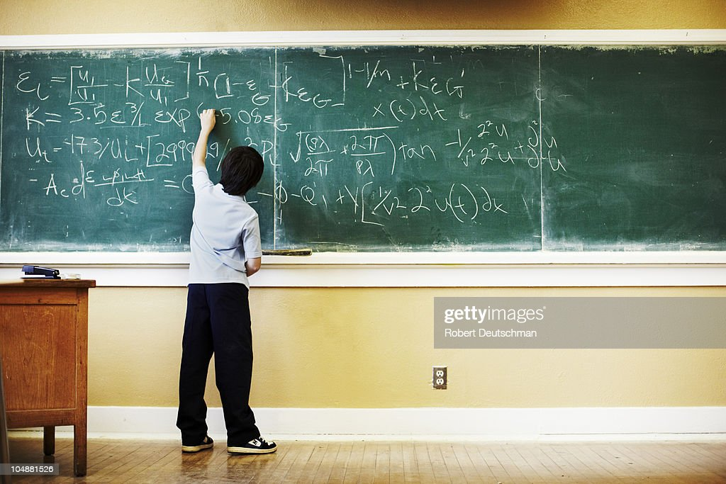Boy doing math at chalkboard : Stock Photo
