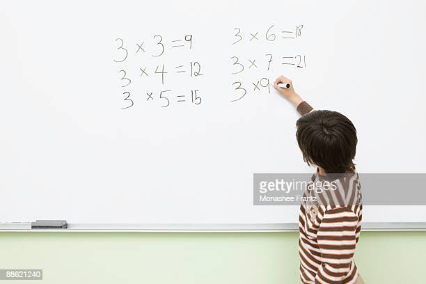 Boy doing multiplication on whiteboard in classroom