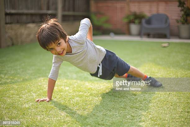 Boy doing one handed push up on grass looking at camera smiling