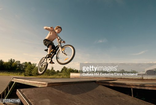 Boy doing tricks on bike : Stock Photo