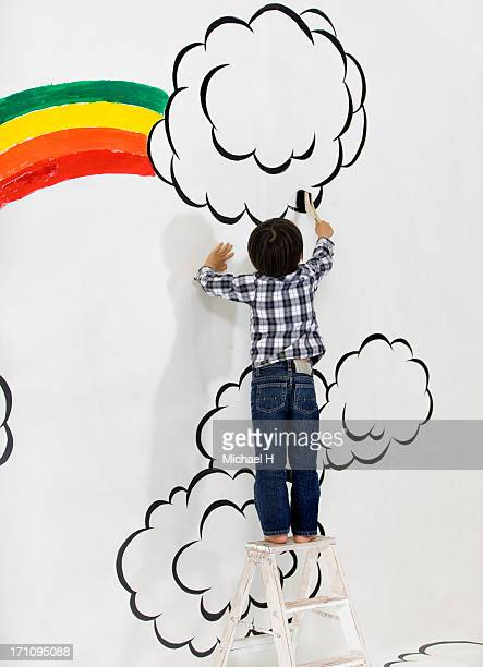 Boy draw rainbow on the wall