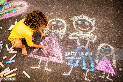 Boy drawing a colourful chalk picture of his family