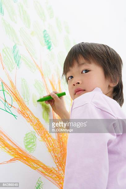 Boy drawing a tree with marker