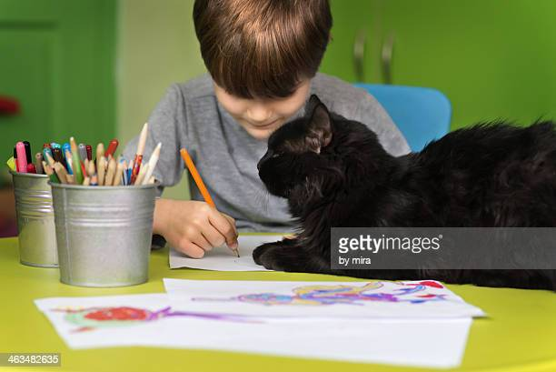 boy drawing and a cat  keeps him company
