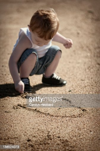 Boy drawing heart in sand : Stock Photo