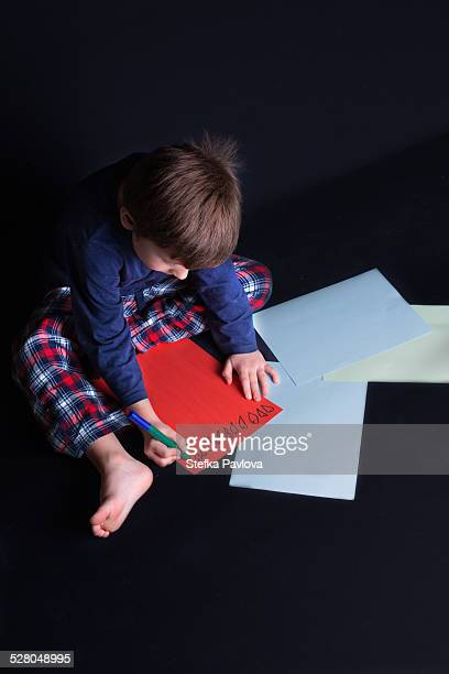 Boy drawing hearts on a sheet of paper
