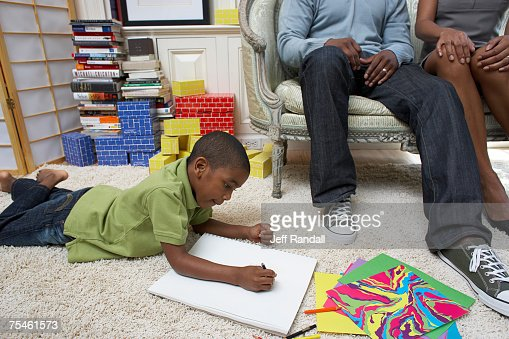 Boy (6-7) drawing in book, parents watching