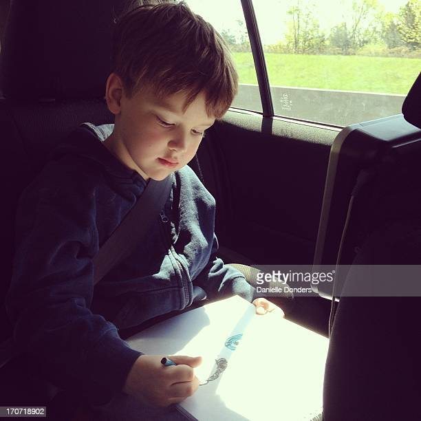 Boy drawing in the car