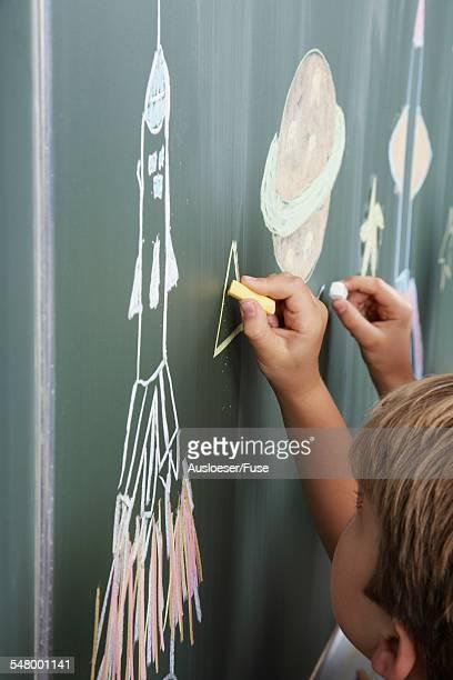 Boy Drawing on Blackboard Drawing