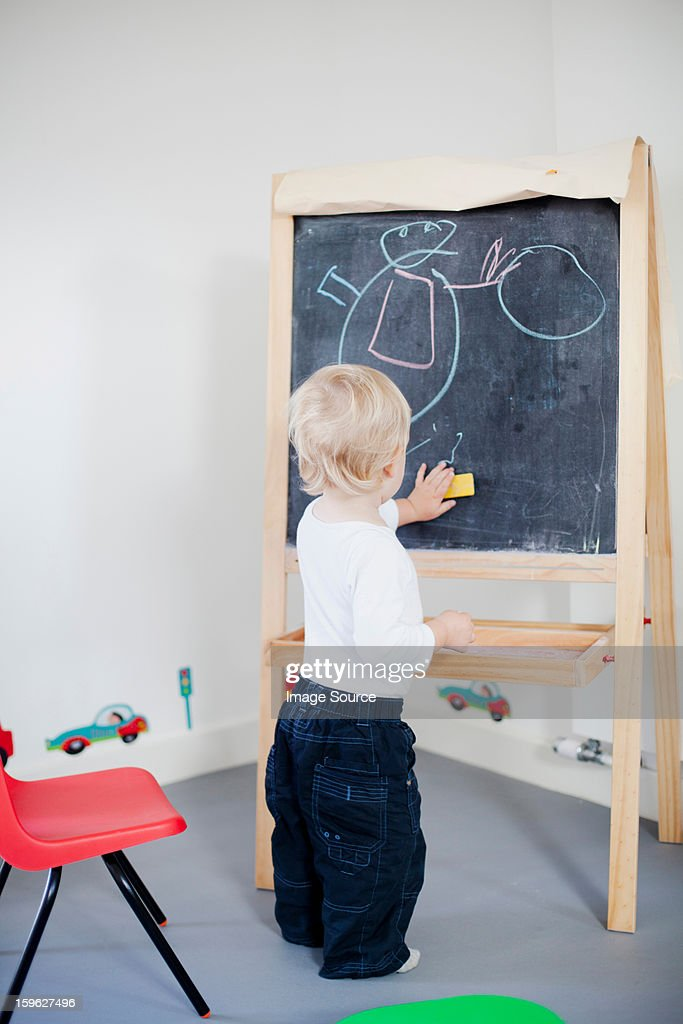 Boy drawing on blackboard : Stock Photo