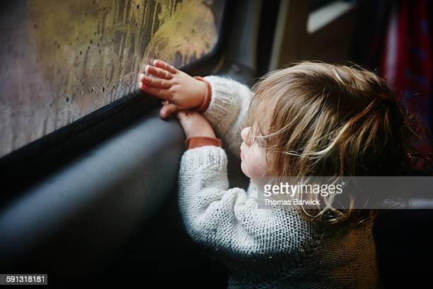 Boy drawing on condensation on window in camper