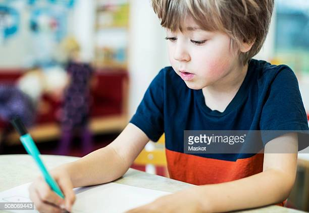 Boy drawing on paper at table in kindergarten