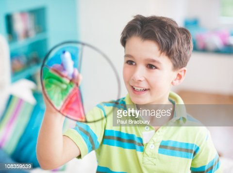 Boy drawing pie chart on glass wall : Stock Photo