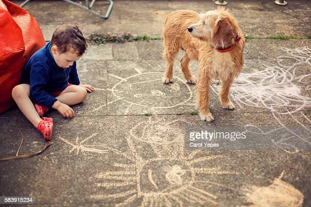 boy ( 3) drawing  with sidewalk chalk with dog